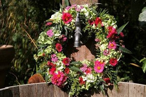 Summer wreath of hydrangeas, asters, sage and grasses hanging on well