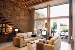 Sofa landscape in a large living room with bank of windows and natural stone and brick wall