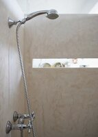 Shower area with concrete walls and wall-mounted hand spray