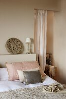 Scatter cushions on bed next to airy curtain in open doorway of simple bedroom