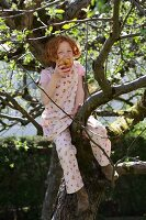 Little girl sitting in a tree eating an apple