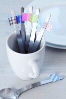 Teaspoons marked with masking tape in a porcelain mug