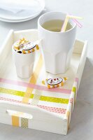 Beaker, drinking straws and toffees on tray decorated with washi tape
