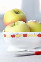 Three apples in china bowl decorated with tape patterned with stylised apples