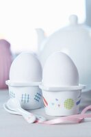 White china egg cups decorated with spots of patterned tape