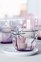 Stylised snowflakes made from thin strips of tape decorating candle lantern with floating candle