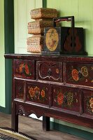Various wooden boxes on wooden chest of drawers painted with floral motifs against green wall