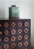 Oriental porcelain jar with lid on wooden chest of drawers painted with patterns