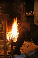 Legs of woman warming herself in front of open fire in old house