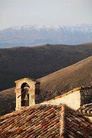 Tiled roof of old Italian church with bell tower and view of mountain landscape