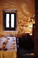 A table laid with small dishes in a rustic dining room with dramatic lighting
