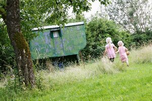 Two little blond girls running to a garden shed