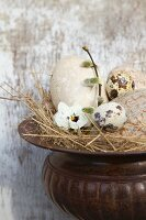 Decorative straw nest with birds' eggs in amphora