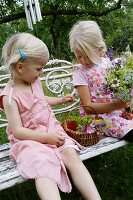 Two blonde girls with flowers sitting on garden bench