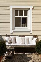Greyed, weathered teak bench with white cushions below window of wooden house