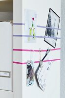 End wall of shelves with elastic bands used as pin board