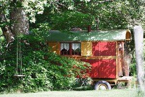 Repurposed circus caravan in thicket of Mediterranean garden with vintage swing on tree