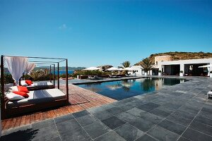 Pool beds and lounge chairs outside by swimming pool