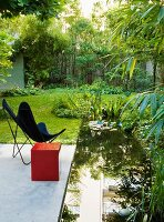 Red cube and butterfly chair on concrete terrace next to small pond