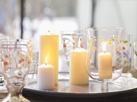 Candles on silver plate and glasses painted with flowers