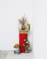 Vase of flowering twigs next to storage jars on end of rolled carpet next to vintage metal bowls on concrete floor