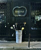 Collection of vintage, metal table lamps in bin in front of old shop with closed window grilles