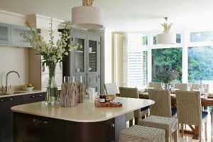 Open-plan kitchen in elegant, maritime, country-house style with rounded square island and wicker chairs at set table in background