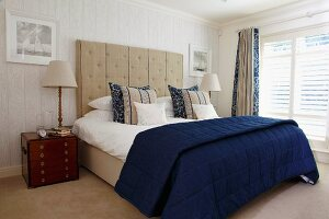 Small wooden chest of drawers and table lamp in English maritime style next to double bed with blue and white bed linen and tall, upholstered headboard