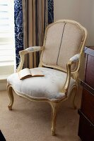 Rococo chair upholstered in two different fabrics in front of matching curtain and on velvet pile carpet in corner of room