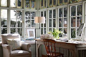 Bright workspace with traditional country-house furniture in bay of latticed windows