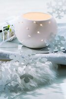 Porcelain tealight holder and stylised paper snowflakes on dish resting on fur