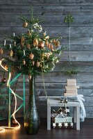 Decorated Christmas tree in vase next to presents on stool against simple wooden wall
