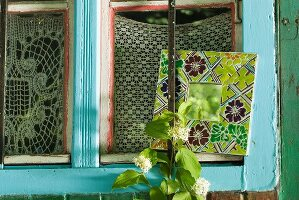 Small mirror with broad floral frame and brightly painted window frame with crochet curtains