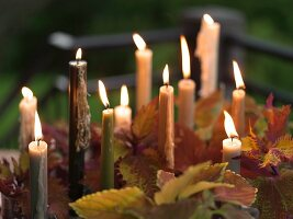 Lit Taper Candles on an Outdoor Table with Leaves