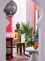 View of wicker sofa, small tables and Oriental pendant lamp through keyhole window