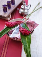 Place setting with tropical flowers on patterned linen napkin; Moroccan silver teapot and tea glasses in background