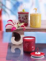 Tealights in coloured, patterned glass holders with decorated lids