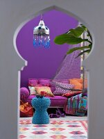 View of blue wicker table and mattress sofa in interior with Oriental ambiance through keyhole window