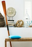 Wooden bench & paddle in front of various ornaments on masonry shelf