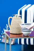Thermos jug with raffia cover next to china bowls on side table