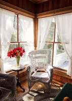 White Wicker Chair by Windows; Table with Red Flowers in a Vase