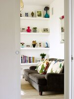 View into a living room - brown sofa with colorful pillows and shelves built into a wall niche
