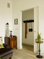 White sliding door between small antique chests of draws with a table lamp made from porcelain greyhound with a houseplant