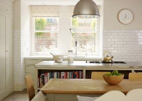 Country-house charm- simple dining table in front of kitchen island with hob and counter with sink below window