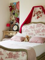Traditional double bed with upholstered headboard and foot next to bedside table in niche below soft toys on pinboard