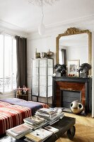 Bedroom with an antique coffee table on wheels next to a bed, fireplace and gold framed mirror