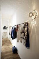 Clothes rod and vintage wall light made from an aluminum colander on a long hallway