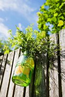Jar of garden flowers hanging on wooden fence