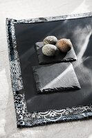 Three pebbles on slate coaster and black place mat with patterned edge