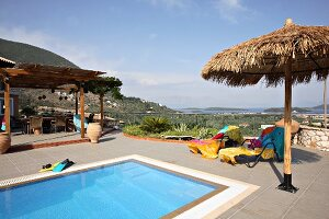 Colourful towels on loungers and parasol next to swimming pool on terrace (Villa Octavius, Lefkas, Greece)
